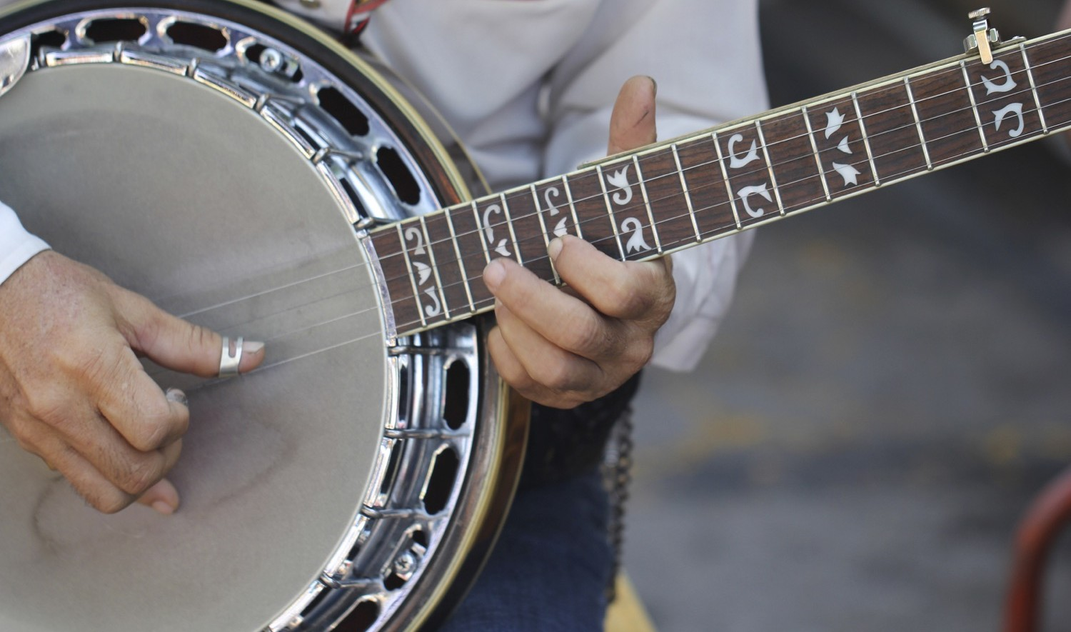 Close up image of a man's hands playing the banjo.
